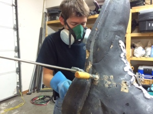 Michael applying fiberglass to repair the statue's right foot